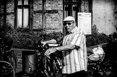 The hidden stare. (Mister G.C.) Tags: street urban photography blackandwhite bw canon canonae1 canonae1program 50mm f18 50mmf18 primelens manual manualfocus slr streetphotography urbanphotography shot image photograph candid people man male guy flatcap sunglasses shades bicycle bike pushbike monochrome town city vintage analog analogphotography 35mm film schwarzweiss strassenfotografie mistergc germany niedersachsen lowersaxony deutschland europe