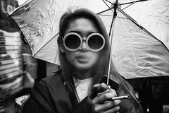 About a girl 137/156 (markfly1) Tags: london camden town girl smoking pretty sunglasses puff smoke cigarette ash rain miserable bad weather umbrella soft shallow focus black white dark shadow bright detail high contrast round rims mobile phone nikon d750 50mm nikkor prime bw bnw mono monochromatic candidphotography day daytime