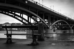 View from a bench of the Wettsteinbrücke over the Rhine river in Basel Switzerland (maxpoll) Tags: basel europe rhine switzerland wettsteinbrücke bw bench blackandwhite bridge city citycentre cityscape day daylight daytime holiday january landmark landscape monochrome outdoor panorama rain rainy river riverside street streetphotography streets view vista winter