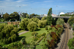 Looking Towards the Port (Jocey K) Tags: newzealand nikond750 southisland timaru buildings architecture trees sky clouds railway gardens port ships cranes