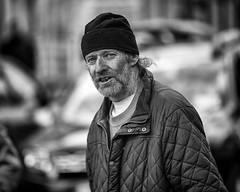 Watching and wondering (Frank Fullard) Tags: frankfullard fullard candid street portrait monochrome ballinasloe horse fair cap beanie face person blackandwhite blanc noir irish irelandwatching wondering beard hair curls
