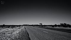 So unresolved, (PhotonenBlende) Tags: westernaustralia westaustralien australia australien road street highway strasse gravel schotter loneliness einsamkeit sky himmel bush busch outback dessert wüste horizon horizont medianstrip mittelstreifen blackwhite bw schwarzweis sw fineart dark dunkel landscape landschaft outdoor landstrase gras einfarbig monochrome