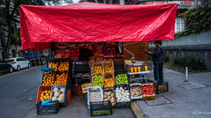 2018 - Mexico City - Condesa - Street Vendor (Ted's photos - For Me & You) Tags: 2018 cdmx cityofmexico cropped mexico mexicocity nikon nikond750 nikonfx tedmcgrath tedsphotos tedsphotosmexico vignetting canopy red redrule oranges fruit vegetables crates streetscene street scale weighscale vehicles onions ginger cantaloupe oj orangejuice curb fencing sidewalk limes mangoes tomatoes bananas apron vendor streetvendor tarp orangepress juicer wheels rope