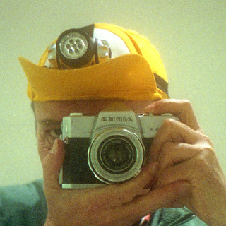 reflected self-portrait with Aries Penta 35 camera and illuminated cap (square crop)