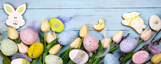 Frame of Sweets for celebrate Easter. Gingerbread in shape of easter bunny, chicken, colorful eggs and tulips