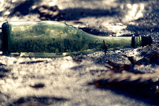 Eine grüne, leere Flasche auf Bokeh-Eis