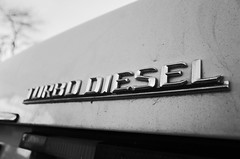 """Turbo Diesel"" (Eric Flexyourhead) Tags: whiterock canada britishcolumbia bc detail fragment car german mercedes mercedesbenz benz turbodiesel badge emblem dirty monochrome blackwhite bw ricohgr"