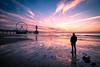 Daydreaming (Zscherny) Tags: sky beach sand pier sundown sun clouds purple violet man waves sea meer netherlands hague colours contrast nature landscape