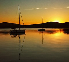 Two boats anchored in a bay at dawn sunrise. Croatia. Stock Photo