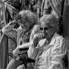 Golden girls (John Riper) Tags: johnriper street photography straatfotografie square vierkant bw black white zwartwit mono monochrome netherlands candid john riper rotterdam marine port worldportdays wereldhavendagen fuji fujifilm xt2 18135 ladies smiling golden girls fence crowd rollator