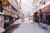 Snow Street (OzGFK) Tags: 35mm akakuraonsen asia fujiindustrial100 honshu japan myokokogen nikkor nikon analog cold film skiing snow snowboarding travel winter wintersports streetphotography cloudy village