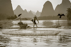 Cast Net in Sepia (lc99photography) Tags: sepia monochrome blackandwhite landscape guilin fisherman cormorant cormorantfisherman cormorantfishing karstformation karst river lijiang liriver splash water mountains birds wildlife man old oldman raft bambooraft china yuanshuo travel