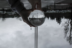 Upside Down (HHolbrook17) Tags: glass glassball flags dim dark school trees flagpoles american flag americanflag parkinglot vancouver washington skyview hands aperture middleground fuzzybackground ngc reflection upsidedown red white blue gray clouds cars tree