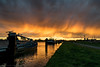 Falling Rain Lit by the Setting Sun (mesocyclone70) Tags: sunset rain sun clouds cloudscape color water ships boats canal holland netherlands weather sky goldenhour grass bay landscape skyscape harbour marina boat ship