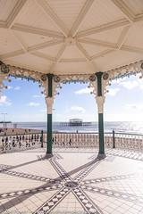 The West Pier framed by the Bandstand, Brighton (Zoë Power) Tags: westpier bandstand beach uk brighton derelict blueskies coast sea seaside