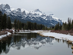 Twice the beauty (annkelliott) Tags: alberta canada wofcalgary birdingtrip rockymountains canadianrockies canmore scenery landscape mountain peak slope range tree trees forest shrub river water ice snow reflection sky outdoor winter 24march2018 canon sx60 annkelliott anneelliott ©anneelliott2018 ©allrightsreserved