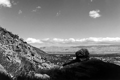 Overlooking Palm Springs (bac1967) Tags: canyon tahquitzcanyon palmsprings palmspringsca palmspringscalifornia california ca kodak tmx tmax kodaktmx kodaktmax kodaktmx100 black white blackandwhite blackandwhitefilm blackwhite bw monochrome monotone kodakmedalist 620 620film landscape clouds boulder rock rockformation sky sagebrush tahquitz cahuilla caliente aguacaliente irrigationditch beerol beerenol pabstblueribbonbeer caffenol