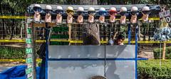 2018 - Mexico City - Chapultepec Park Vendor (Ted's photos - For Me & You) Tags: 2018 cdmx cityofmexico cropped mexico mexicocity nikon nikond750 nikonfx tedmcgrath tedsphotos tedsphotosmexico vignetting precaucion sunglasses cart wheel manequins goggles fence chain fencing shadow shadows chapultepec chapultepecpark red redrule
