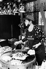 Receiving orders (Go-tea 郭天) Tags: xiamen food sea omelette candid cook cooking station shop business eggs pan oil tools fried portrait woman lady chef cap busy work working clients customers orders duty spots street urban city outside outdoor people bw bnw black white blackwhite blackandwhite monochrome naturallight natural light asia asian china chinese canon eos 100d 24mm prime hot warm xiamenshi fujiansheng chine cn