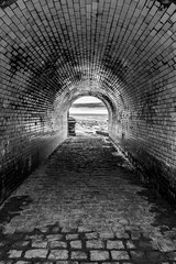 Tunnel (Niaic) Tags: blackandwhite monochrome tunnel texture contrast tiles curve arc arch beach coast front sea mud sand merseyside cobble cobbles through path route wall walls