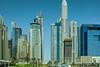 Dubai skyline (Marian Pollock) Tags: middleeast dubai skyscrapers skyline sky cars signs dome palms road street park landmarkgroup emaar arabemirates urban city shukran angular bluesky design fencing