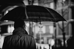 dandyism (tomorca) Tags: rain umbrella man bokeh street monochrome blackandwhite voigtlander nokton 58mm fujifilm xt2