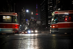 Passing In The Night (Paul Flynn (Toronto)) Tags: torontotransitcommission toronto transit commission ttc streetcar road street university dundas city lights night crosswalk cntower canada life transportation car cars public