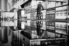 XXANAXX 191.365 (ewitsoe) Tags: monochrome blackandwhite bnw bike ride rider man reflection city cityscape urban billboards fence walk ewitsoe canon 6dii street ecplore travel race water puddle sidewalk riding