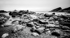 Amongst the stones (NikNak Allen) Tags: plymouth devon heybrookbay beach sand stone rock rocks damp water sea coast ocean bay horizon jagged sky seascape low morning early pov light shadows grey greys black white blackandwhite longexposure