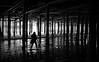 Under the pier (Gael Varoquaux) Tags: pier monochrome sea waves woman vertical dark atmosphere