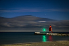 Beacon under the Stars (T P Mann Photography) Tags: lighthouse light reflections green red stars night sky clouds seascape sea lake michigan charlevoix lakemichigan pier ice railing water longexposure beach shore sand rocks storm stormfront