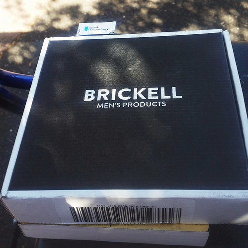 "A cardboard box, perhaps eight inches square and an inch high, with the words ""Brickell Men's Products"" in white on a black lid.  The box rests on top of a paperback book, and it has a barcoded sticker on the bottom of its front."