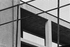 Forefenced (Thomas Listl) Tags: thomaslistl blackandwhite noiretblanc biancoenegro filmphotography analog fence grid hff grey diagonal lines architecture minoltax700 ilford hp5 hp51600 pushto1600 pushingfilm