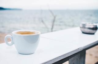 Coffee break at a beach bar. Sea background.