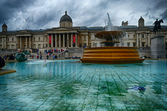 Trafalgar Square in London, United Kingdom (` Toshio ') Tags: toshio london england unitedkingdom greatbritain british nationalgallery fountain water architecture clouds storm rain square people museum fujixt2 xt2 flag statue column dome