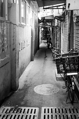 Waiting (Go-tea 郭天) Tags: xiamenshi fujiansheng chine cn xiamen old ancient narrow alley man motorbike motorcycle motobike motocycle bicycle byke motobyke alone lonely candid wait waiting dark shadow cables electric electricity dirty young street urban city outside outdoor people bw bnw black white blackwhite blackandwhite monochrome naturallight natural light asia asian china chinese canon eos 100d 24mm prime empty