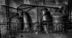 Oil Cans (arbyreed) Tags: arbyreed oil oilcans oldoilcans vintageoilcans wideaspectratio dark monochrome bw blackandwhite textures monochrometextures metal metalic wood legends legendsmotorcycleemporium sidecarcafe motorcycles vintagemotorcycles indianmotorcycles