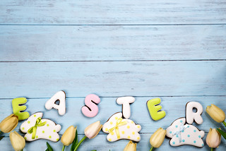 Sweets for celebrate Easter. Gingerbread in shape of easter bunny and letter Easter, tulips