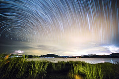 Star Lines and Storm Trails (Matt Molloy) Tags: mattmolloy timelapse photography timestack photostack movement motion night sky stars trails lines milkyway clouds storm lightning wind green grass lights water mountains boats boathouseparadiseresort kaengkrachan lake phetchaburi thailand landscape nature countryside lovelife