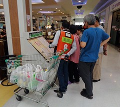 looking for their lucky numbers (the foreign photographer - ฝรั่งถ่) Tags: crowd people lottery tickets shopping cart tesco lotus supermarket laksi bangkhen bangkok thailand sony