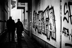 ANTiFA (Mister G.C.) Tags: street urban photography blackandwhite bw canon canonae1 canonae1program 50mm f18 50mmf18 primelens manual manualfocus slr streetphotography urbanphotography shot image photograph candid people alley alleyway sidestreet gaffiti spraypainting vandalism gritty frombehind monochrome town city vintage analog analogphotography 35mm film schwarzweiss strassenfotografie mistergc germany niedersachsen lowersaxony deutschland europe