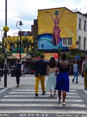 Time to Samba (Steve Taylor (Photography)) Tags: samba jointheparty streetfood graffiti mural streetart street blue yellow orange people women ladies men man uk gb england greatbritain unitedkingdom london whitechapel dancer mustard star lookbothways crossing rays carmenmiranda