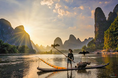 A Bird in Hand (Hilton Chen) Tags: cormorantfisherman autumn guangxiprovince landscape sunset bambooraft xingpingfishingvillage guilin birds portraitinthelandscape liriver karstmountains fishingnet china sunburst guilinshi guangxizhuangzuzizhiqu cn