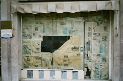 Tanger طنجة (slo:motion) Tags: طنجة tanger morocco africa contaxt2 fuji provia400x abandoned windows window reflection newspaper storefront store shop shopfront