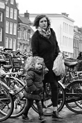 City Life (d_t_vos) Tags: mother woman child girl littlegirl daughter two people outside street streetphotography streetportrait portrait bikes bicycle bicycles buildings winter wintercoat cold nervous jumpy agitated anxious fearing insecure uncertain doubtful leeuwarden nieuwestad bw blackandwhite zwartwit cross crossover dickvos dtvos