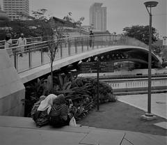 at the end of the rainbow (SM Tham) Tags: asia southeastasia malaysia kualalumpur klcolonialwalk bridge girls people buildings riverside river lamppost shrubs plants monochrome blackandwhite