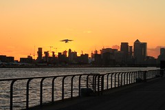 Take Off (Michael Adedokun) Tags: londoncityairport takeoff canarywharf water skyline london londonskyline planespotting sunset spring metalfence riverthames