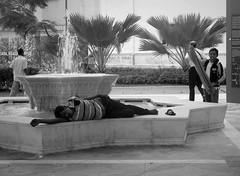 life goes on (SM Tham) Tags: asia southeastasia malaysia kualalumpur klcolonialwalk masjidjamek jamekmosque forecourt marble fountain water man sleeping people palms blackandwhite monochrome streetphotography