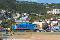 Kids playing in a field with blue tarps in the backgroud, St Thomas Virgin Islands