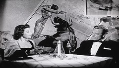 "Dr. Scott (Richard Denning) and Teresa Alvarez (Mara Corday) out clubbing in ""The Black Scorpion"" (1957) (lhboudreau) Tags: movie motionpicture film classicsciencefictionmovie sciencefictionfilm sciencefiction scifi classicsciencefiction classicscifi monster threat screenshot monstermovie monsterfilm 1950s giantinsects blackandwhite blackwhite featurefilm scarymovie monochrome 1957 warnerbros warnerbrothers warner edwardludwig jackdietz frankmelford blackscorpion theblackscorpion giant specialeffects stopmotion stopmotionanimation animation obrien willisobrien petepeterson people retro vintage richarddenning drhankscott ranchowner scientist geologist mexico teresaalvarez maracorday club date art artwork bullfight bullfighter bull wallart drinks bowtie toast table candle moviestars actors actor"